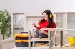 El contratista femenino que repara los muebles en casa fotos de archivo libres de regalías
