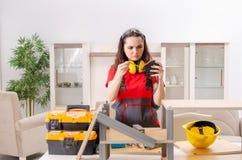El contratista femenino que repara los muebles en casa fotografía de archivo