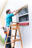 El contratista mide la ventana Foto de archivo libre de regalías