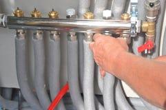 El contratista que instala, sistema de calefacción de piso de la reparación con el metal aislado instala tubos foto de archivo