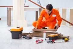 El contratista que trabaja en piso de madera laminado imágenes de archivo libres de regalías