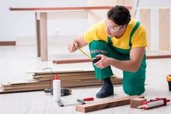 El contratista que trabaja en piso de madera laminado fotos de archivo