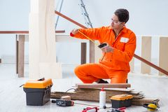 El contratista que trabaja en piso de madera laminado imagen de archivo libre de regalías