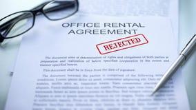 El contrato de alquiler de la oficina rechaz?, mano que sellaba el sello en el documento de negocio, cierre imagen de archivo