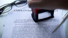 El contrato de empleo, funcionarios da el sellado del sello en el documento de negocio, cierre para arriba imagen de archivo