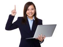 El control asiático de la empresaria con el ordenador portátil y el finger señalan Foto de archivo libre de regalías
