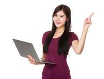 El control asiático de la mujer con el ordenador portátil y el finger señalan hacia arriba Imagenes de archivo