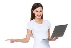 El control asiático de la mujer con el ordenador portátil y el finger señalan a un lado Imagen de archivo libre de regalías
