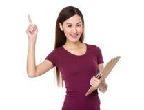 El control asiático de la mujer con la carpeta y el finger señalan hacia arriba Fotos de archivo libres de regalías