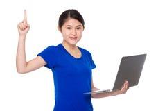 El control de la chica joven con el ordenador portátil y el finger destacan Imagenes de archivo