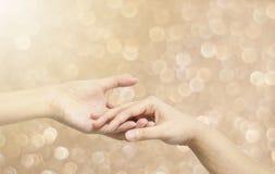 El control de la mano de la mujer del primer otra mano de la mujer para la consola y anima en la emoción blanda en bokeh marrón b Fotos de archivo libres de regalías
