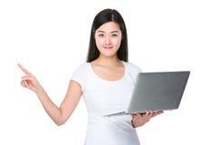 El control de la mujer con el ordenador portátil y el finger destacan Fotos de archivo