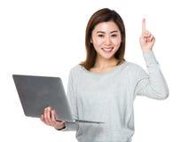 El control de la mujer con el ordenador portátil y el finger destacan Foto de archivo