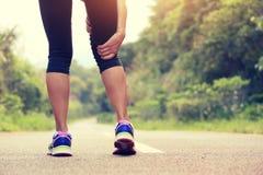 El control del basculador de la mujer de la aptitud sus deportes hirió la pierna en el rastro del bosque Imágenes de archivo libres de regalías