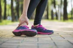 El control del corredor de la mujer torció el dolor del tobillo, pierna humana Imágenes de archivo libres de regalías
