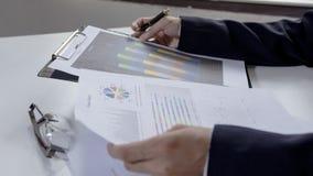 El control del hombre de negocios analiza seriamente a los colegas de las finanzas de un inversor del informe que discuten datos  imagenes de archivo