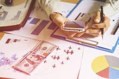 El control del hombre de negocios llama por teléfono para comprobar trabajos y gráficos con los dólares o el dólar de EE. UU. de  Foto de archivo libre de regalías