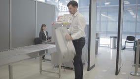 El control del hombre de negocios un equipaje en la máquina de radiografía y pasa a través de punto de control de la radiografía almacen de video