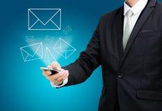 El control derecho de la mano de la postura del hombre de negocios que el teléfono móvil envía el correo es foto de archivo libre de regalías