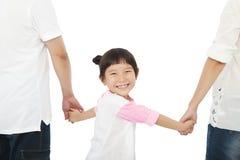 El control feliz de la niña parents las manos y la sonrisa Foto de archivo libre de regalías