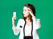 El control tailandés asiático de la muchacha compone la cara con el teléfono móvil Imagenes de archivo
