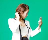 El control tailandés asiático de la muchacha compone la cara con el teléfono móvil Fotos de archivo libres de regalías