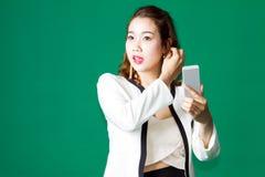 El control tailandés asiático de la muchacha compone la cara con el teléfono móvil Imágenes de archivo libres de regalías