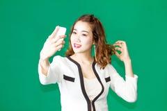 El control tailandés asiático de la muchacha compone la cara con el teléfono móvil Fotografía de archivo libre de regalías