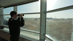 El controlador aéreo está mirando en distancia en aeropuerto con los prismáticos almacen de metraje de vídeo