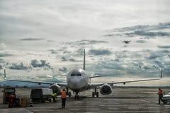 El controlador aéreo toma el cuidado de aterrizar un aeroplano en el aeropuerto, mientras que otro está volando en el cielo imagen de archivo