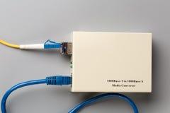 el convertidor de los medios ópticos 1Gbps con el módulo de SFP conectó con el cordón de remiendo del cordón y del cobre de remie Foto de archivo libre de regalías