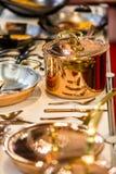 El cookware, los potes y las cacerolas de cobre están en el contador en la tienda imagenes de archivo