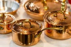 El cookware, los potes y las cacerolas de cobre están en el contador en la tienda Fotos de archivo libres de regalías