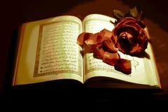 El Corán con una rosa imagenes de archivo