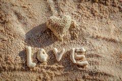 El coral en forma de corazón y la palabra AMAN en la arena, isla de Boracay, Filipinas Fotografía de archivo