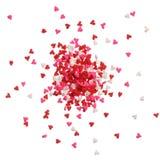 El corazón asperja en rojo, rosa y blanco en una pila foto de archivo