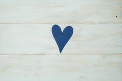 El corazón azul en un fondo blanco, madera pintó el azul griego Fotografía de archivo