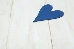 El corazón azul en un fondo blanco, madera pintó el azul griego Foto de archivo