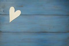 El corazón blanco en un fondo azul, madera pintó el azul griego Fotografía de archivo