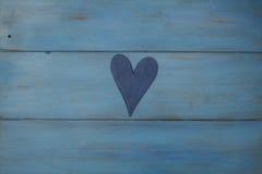 El corazón blanco en un fondo azul, madera pintó el azul griego Imagen de archivo libre de regalías