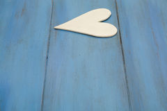 El corazón blanco en un fondo azul, madera pintó el azul griego Foto de archivo