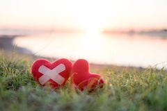 El corazón con yeso y el corazón rojo en el fondo, el sol cae fotos de archivo