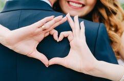 El corazón de la boda con sus manos ama a su marido Compañerismo de la boda amor detrás de su parte posterior foto de archivo libre de regalías