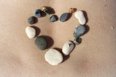 El corazón de la piedra cae el cuerpo del agua Imágenes de archivo libres de regalías