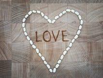 El corazón de las piedras blancas en la superficie de madera Fotografía de archivo libre de regalías