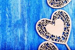El corazón de madera talló en un fondo de madera azul Fotos de archivo