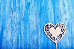 El corazón de madera talló en un fondo de madera azul Fotografía de archivo libre de regalías