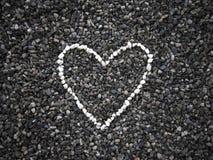 El corazón de pequeñas piedras blancas en las piedras oscuras emerge Fotos de archivo libres de regalías