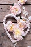 El corazón decorativo y las peonías rosadas florece en backgr de madera envejecido fotos de archivo libres de regalías