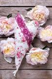 El corazón decorativo y las peonías rosadas florece en backgr de madera envejecido foto de archivo libre de regalías